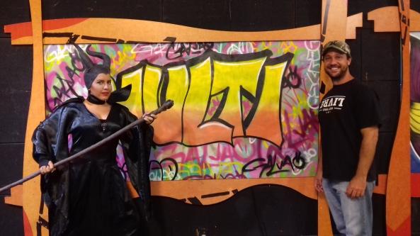 Lua fazendo cosplay de Malévola ao lado do grafiteiro Diogo Galvão